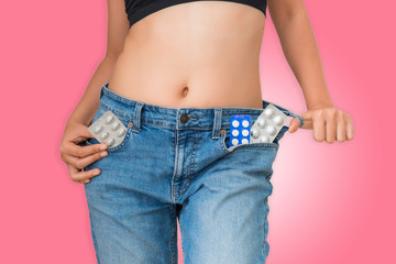 Portrait of young woman showing diet pills in her jeans pocket, Healthcare and medical concept