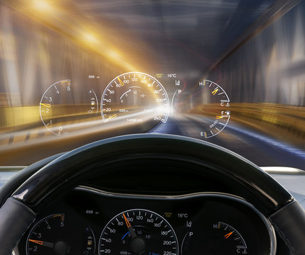 car equipped with a display on the HUD  driving at night illuminated by a tunnel