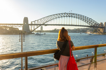 Female tourist with backpack bag  taking photos of Sydney Harbour Bridge during summer vacation trip.