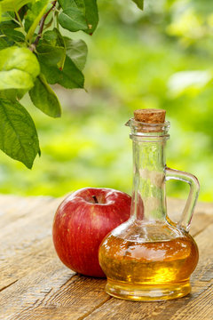 Apple vinegar in glass bottle and fresh red apple on wooden boar
