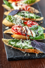 Italian bruschettes with mozzarella cheese, tomatoes, pesto sauce and parmesan cheese, on a black stone, on a wooden table. Copy space, selective focus