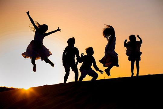 five children jump at sunset