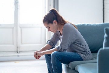 Young attractive latin woman lying at home living room couch feeling sad tired and worried suffering depression in mental health, problems and broken heart concept.