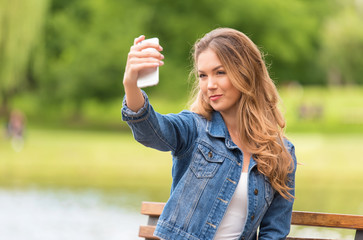 Beauty woman taking selfie with her phone in nature