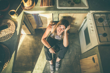 Smiling girl sitting on the kitchen floor. Funny picture of a girl in the kitchen