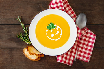 Squash Soup with Parsley. Fresh homemade cream of Carrot and Pumpkin  soup with a swirl of cream  on dark wooden table. Top view