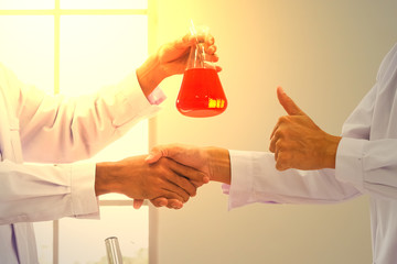 Man handshake to welcome the success of scientific chemical research.