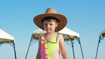 b6cf434b764e8 0 09 Child on vacation with a hat. Beautiful little girl on the beach  wearing a cowboy