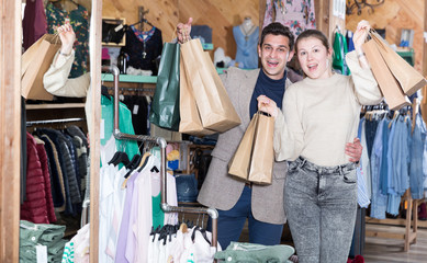 Young woman and man are standing satisfied with packadge after shopping