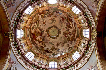Cathedral dome with religious fresco - Christian paintings on a ceiling of St. Nicolas cathedral in Prague