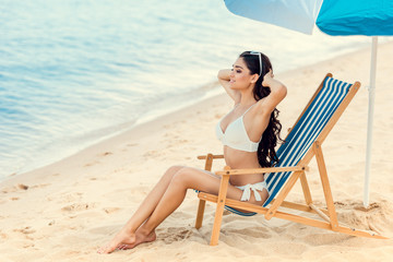 attractive girl sitting on beach chair under umbrella near the sea