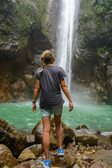Young girl hikers looking at the tropical waterfall in the jungles of Asia. Negros Island Philippines.
