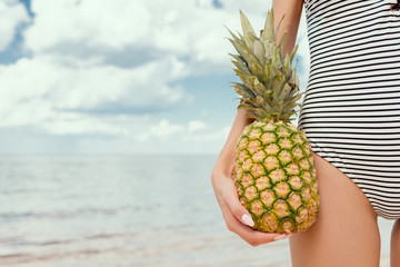 cropped view of woman in swimsuit holding fresh pineapple near the sea