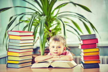 Back to school and happy time! Cute industrious child is sitting at a desk indoors.