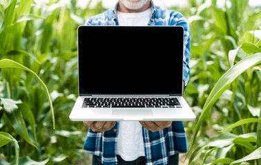 Farmer in the field showing laptop screen, closeup