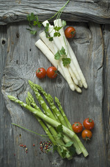 Green and white asparagus, parsley, tomatoes and mixed peppercorns on wood