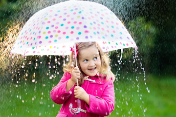 Little girl with umbrella in the rain