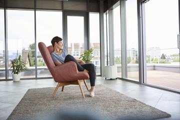 Woman sitting in armchair at home looking out of balcony door