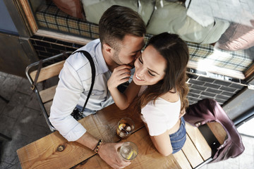 Affectionate couple having drink at outdoor cafe