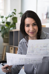 Portrait of smiling woman holding sheets of paper in office