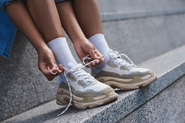 Young woman free style on the street sitting on stairs tying sho