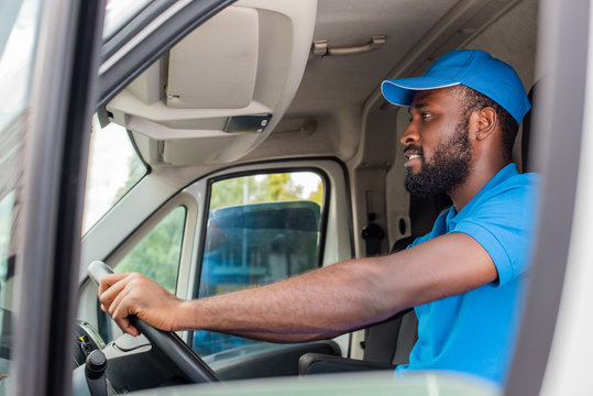 side view of african american delivery man driving van