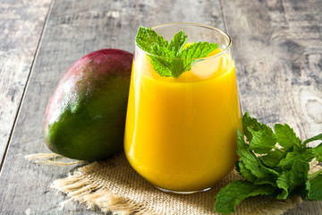 Mango Lassi dessert. Traditional Indian drink on wooden table.