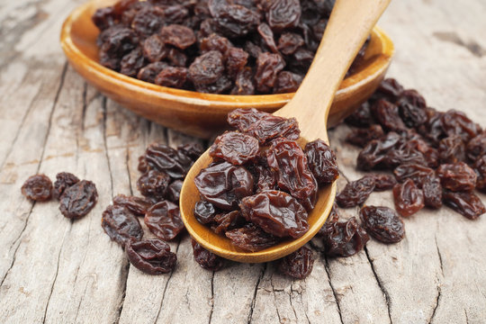 Organic dried Raisins in wood spoon on wooden table, Currant