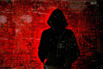 Male figure with hood on red wall background. Hacker concept.