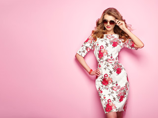 Blonde young woman in floral spring summer dress. Girl posing on a pink background. Summer floral outfit. Stylish wavy hairstyle. Fashion photo. Glamour lady in stylish sunglasses