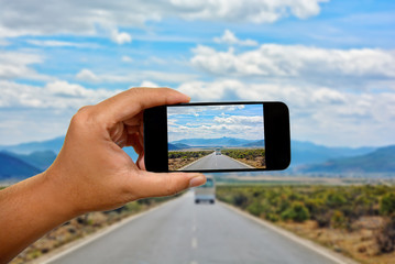 Take a photo with a mobile phone in Road in the middle of natural mountain landscape with a van and car on the road with blue sky background