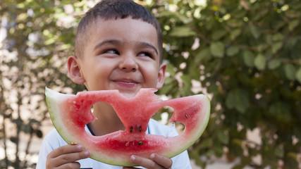 Boy looking through heart shape hole in a watermelon