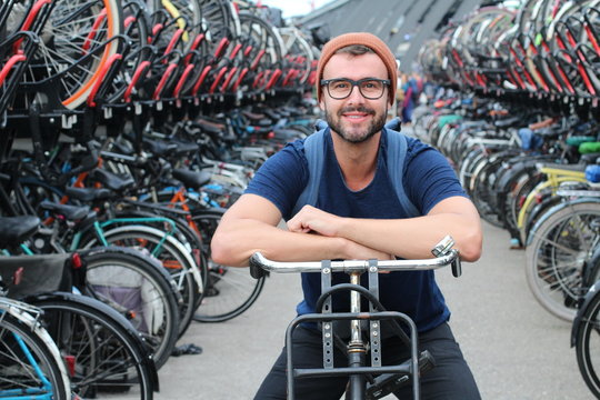 Man giving smiling at bicycle parking lot