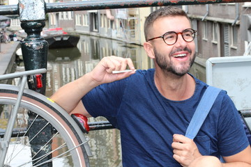Man smiling in Amsterdam while holding joint