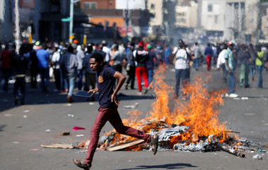 A man runs as supporters of the opposition Movement for Democratic Change party (MDC) of Nelson Chamisa burn barricades in Harare