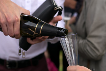 the hand of the man in the white shirt pours champagne on a holiday in the open air