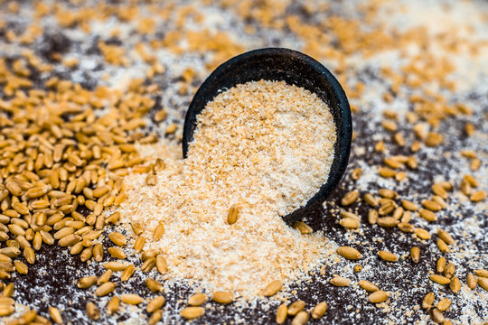 Close up of oats in a black colored clay bowl on wooden surface with wheat grains in surroundings.