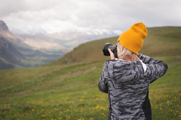 A young girl takes pictures of a plateau on top of a high mountain on a cloudy day. View of the girl behind