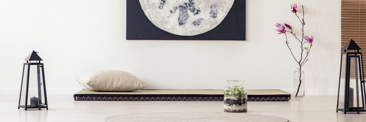 Moon poster above futon in japanese bedroom interior with flowers and lanterns. Real photo
