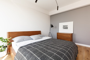 Patterned grey blanket on wooden bed in hotel bedroom interior with poster above cabinet. Real photo