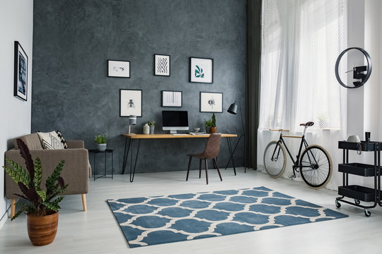 Patterned carpet in bright workspace interior with bicycle next to brown chair at desk. Real photo