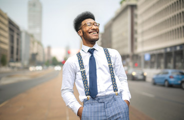 Stylish man laughing while walking in the street