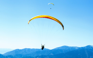 Zelfklevend Fotobehang Luchtsport Two Paragliders soaring in the sky over the blue mountains