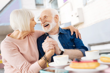 Life together. Low angle of cheerful senior couple holding hands and laughing