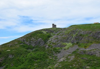looking up from the hiking path on the bottom of Signal Hill covered with lush green grass towards the tower, St John's Newfoundland Canada