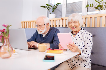 Modern approach. Attractive senior man using laptop and senior woman holding tablet