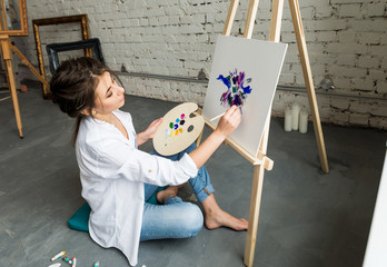 Beautiful brunette girl in white shirt and jeans, sitting at work place and creating, drawing picture with oil colorful paints. Pretty woman, female artist holding brush and palette. Concept of art.