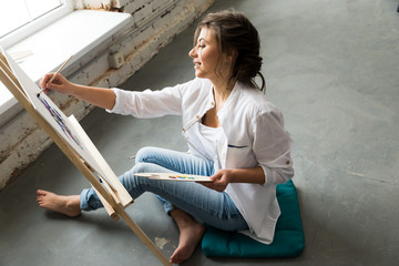 Beautiful brunette girl in white shirt and jeans, sitting at work place and creating, drawing picture with oil colorful paints. Pretty woman, female artist holding brush and palette and smiling.