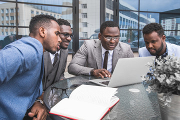 Group of happy diverse male business afro - american people team in formal gathered around laptop computer in bright office against the background of a glass building