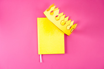 top view of yellow notebook with paper crown on pink